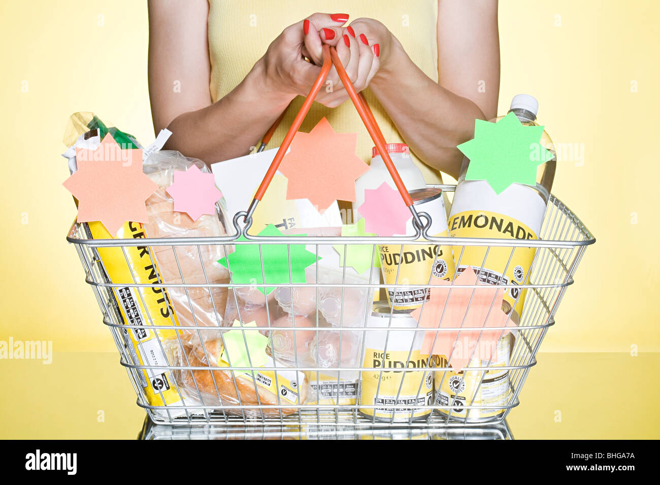 Woman with basic groceries in basket - Stock Image