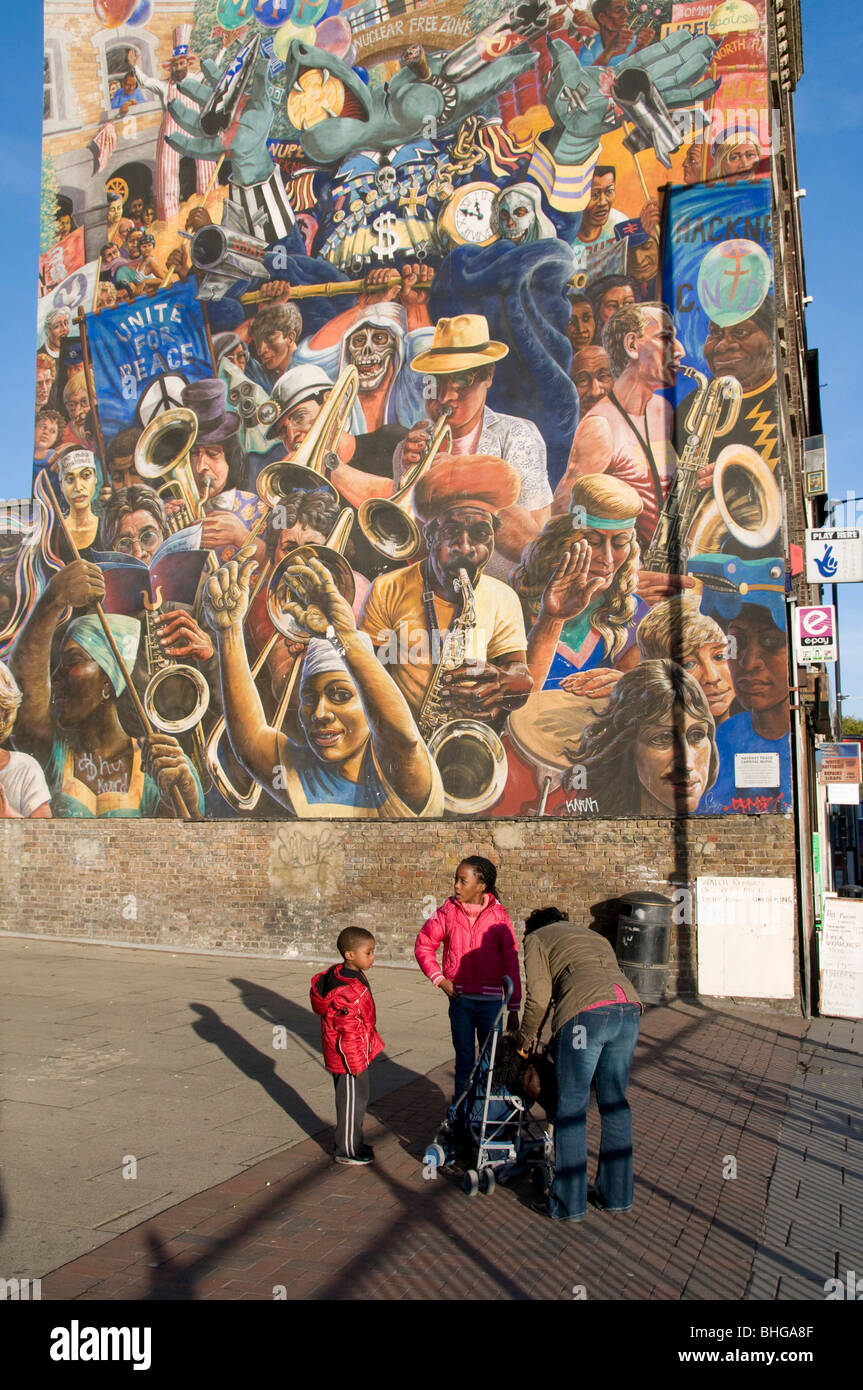 AFRO-CARIBBEAN FAMILY BY A COMMUNITY MURAL IN HACKNEY, LONDON UK - Stock Image