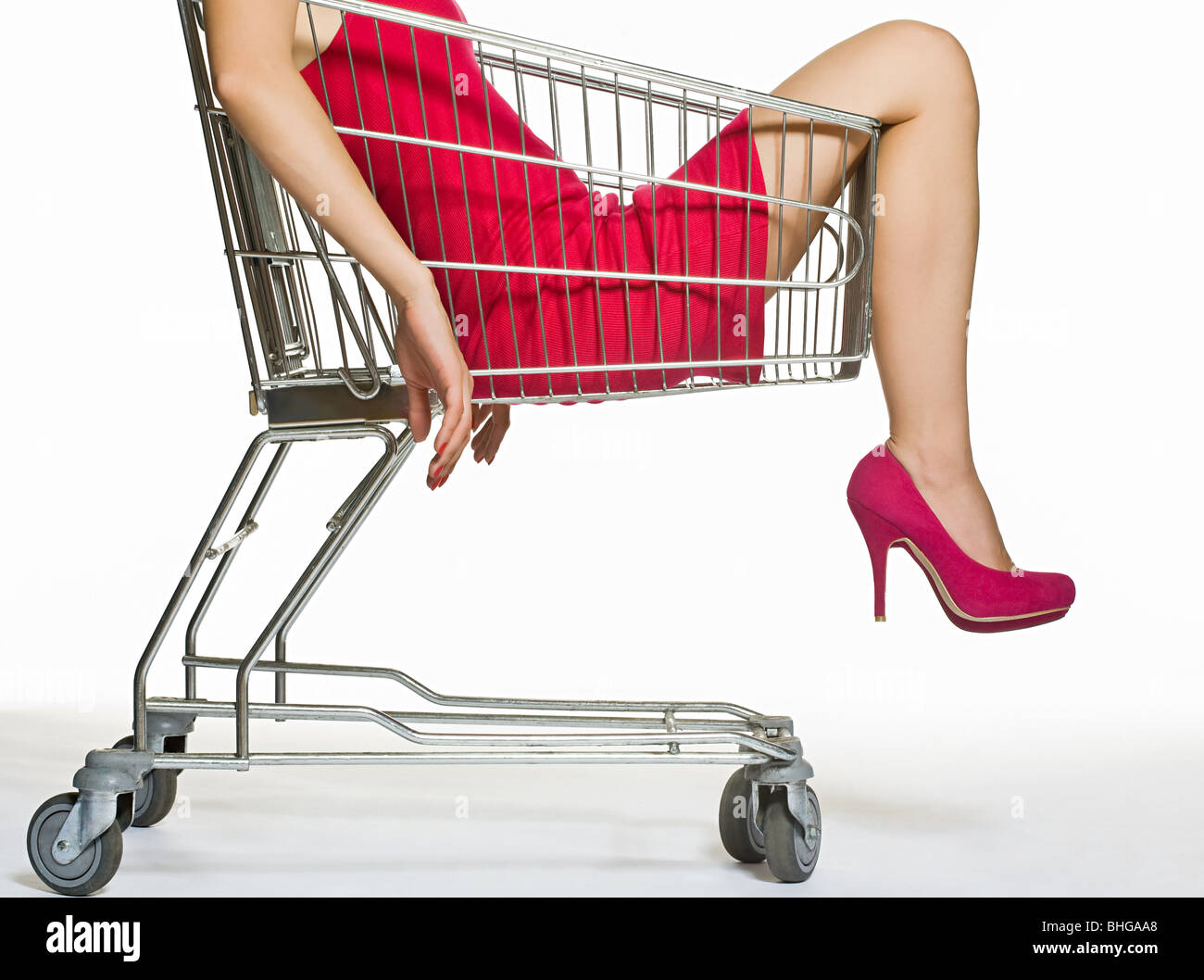 Woman in a shopping trolley - Stock Image