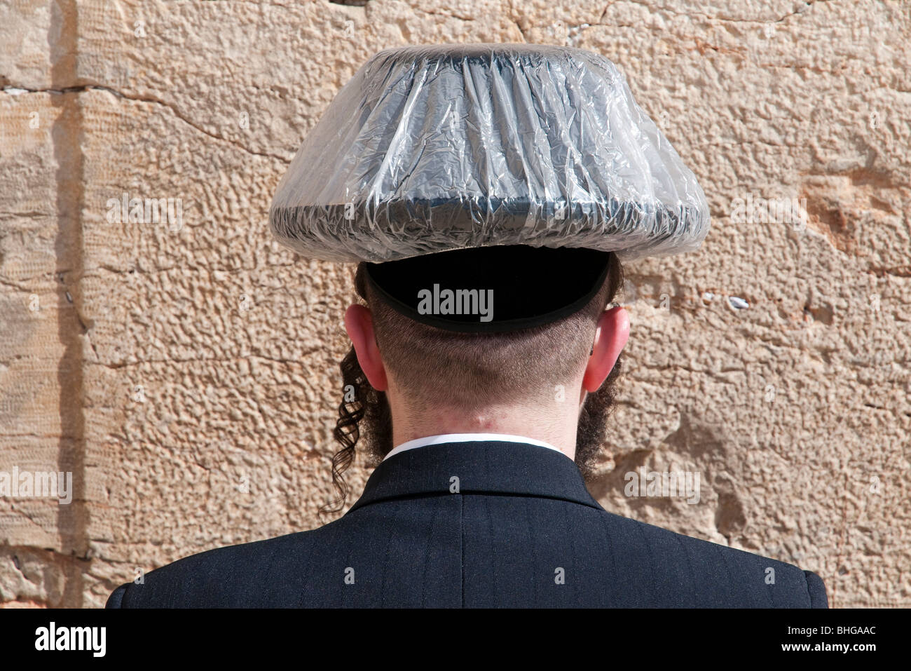 orthodox jew with hat wrapped in plastic bag praying at western wall - Stock Image
