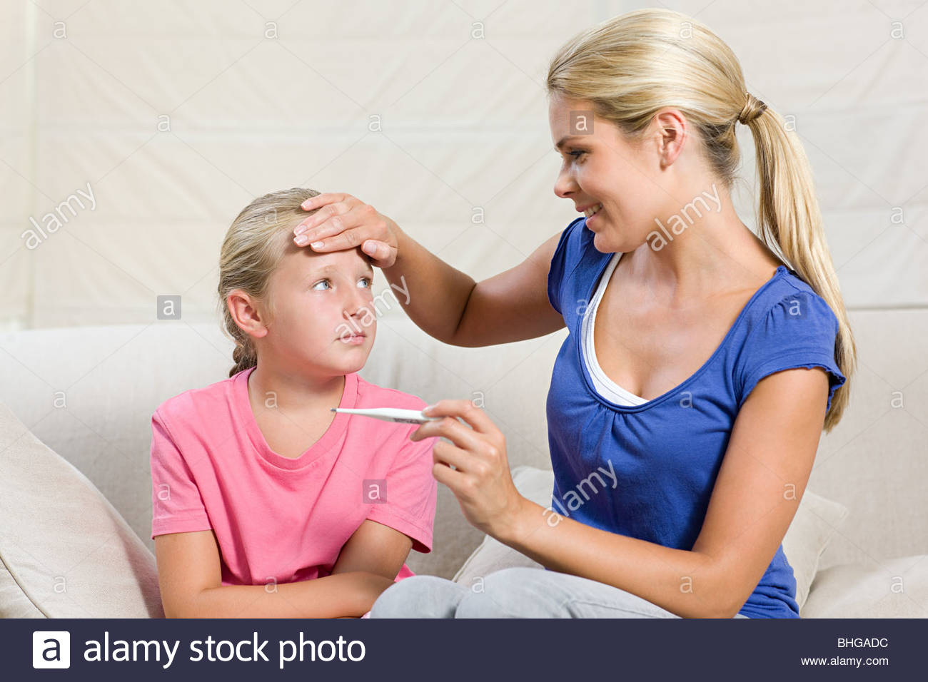 Ill girl and mother with thermometer - Stock Image