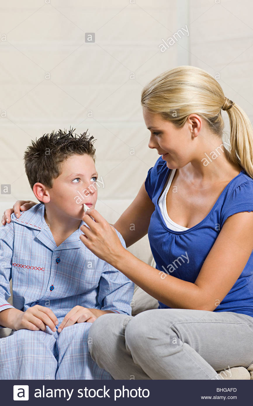 Ill boy and mother with thermometer - Stock Image