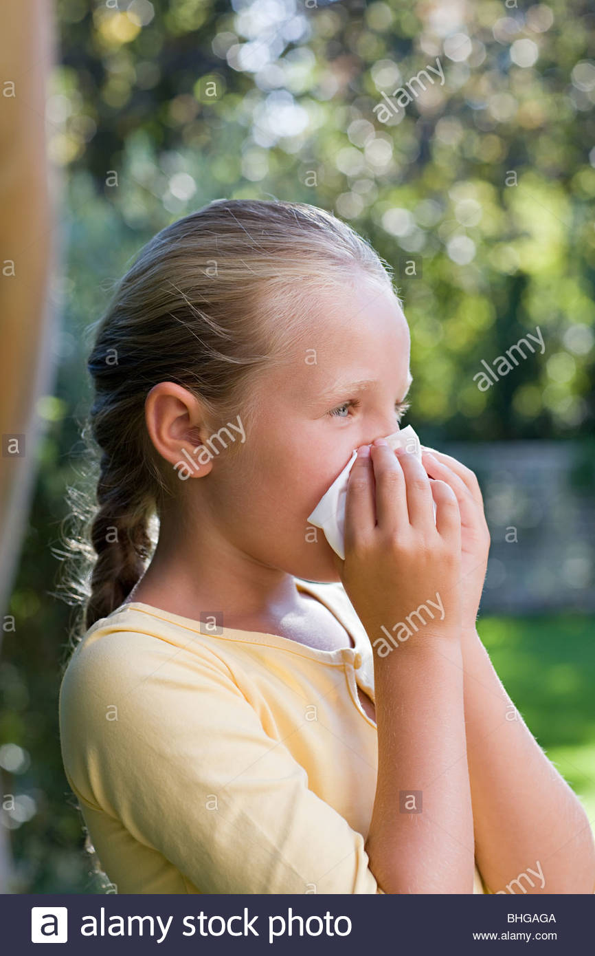 Girl blowing nose - Stock Image