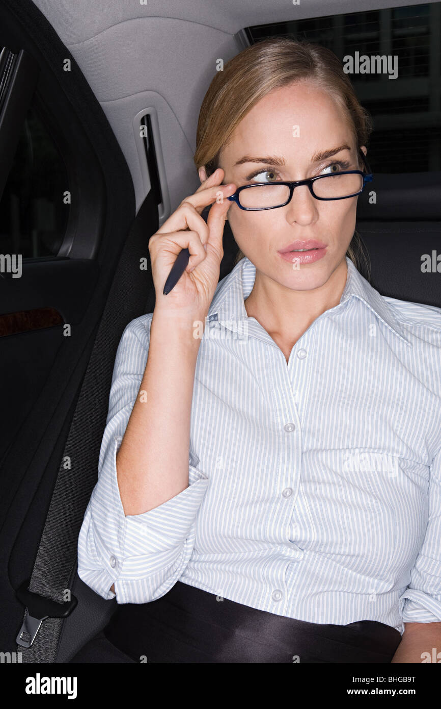 Businesswoman adjusting her eyeglasses - Stock Image
