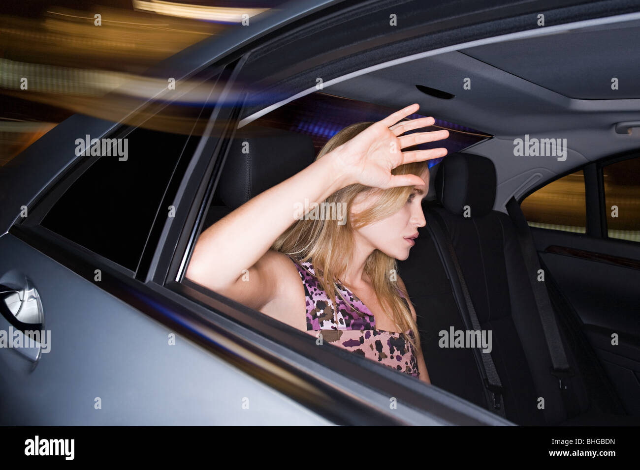 Woman with hand raised to car window - Stock Image