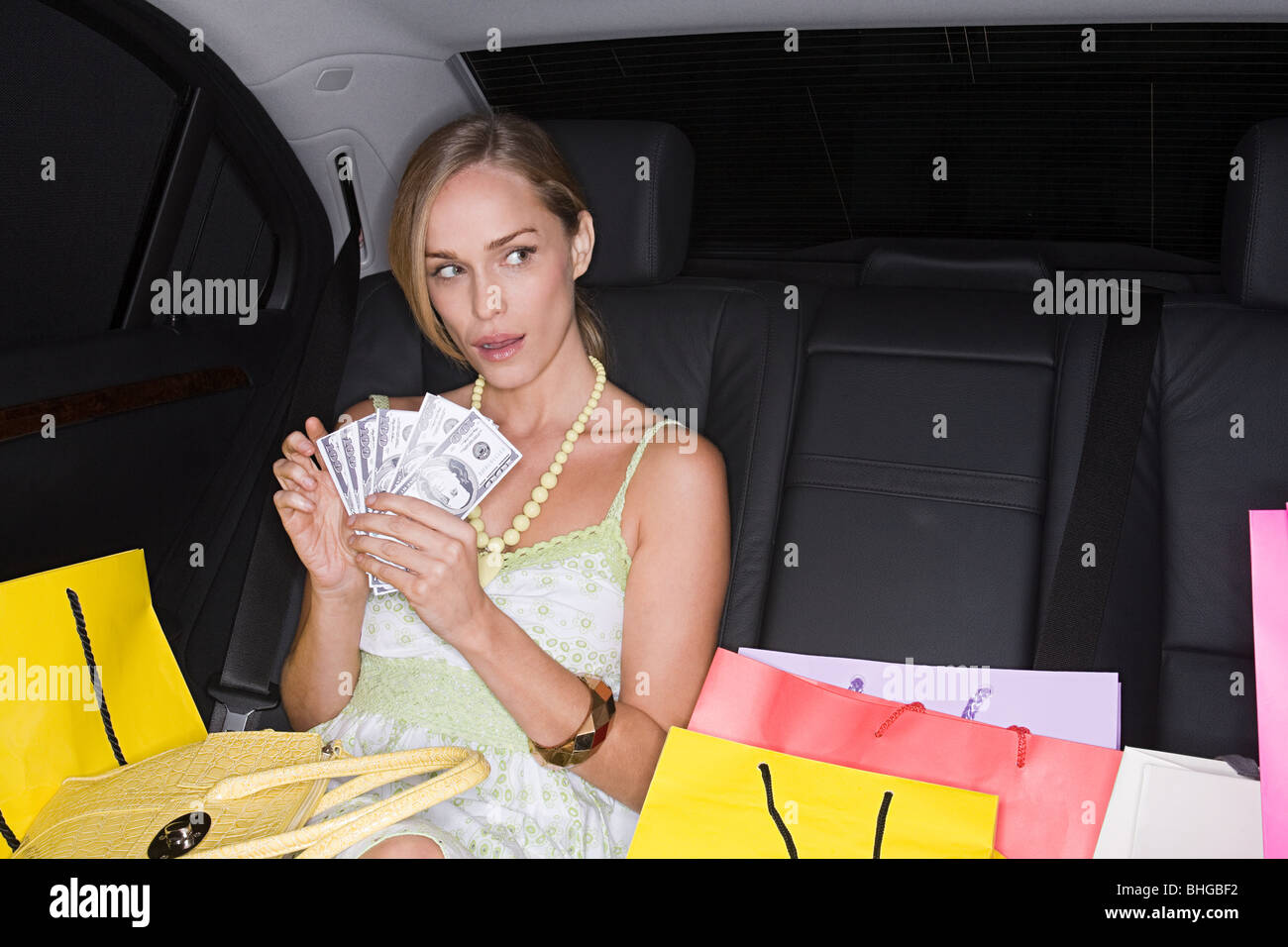 Woman with shopping bags and cash in a car - Stock Image