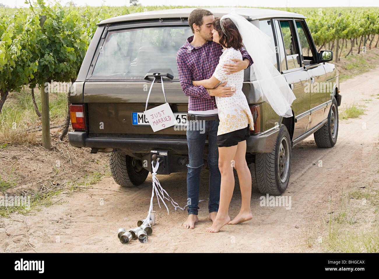 Newlywed couple kissing by vehicle - Stock Image
