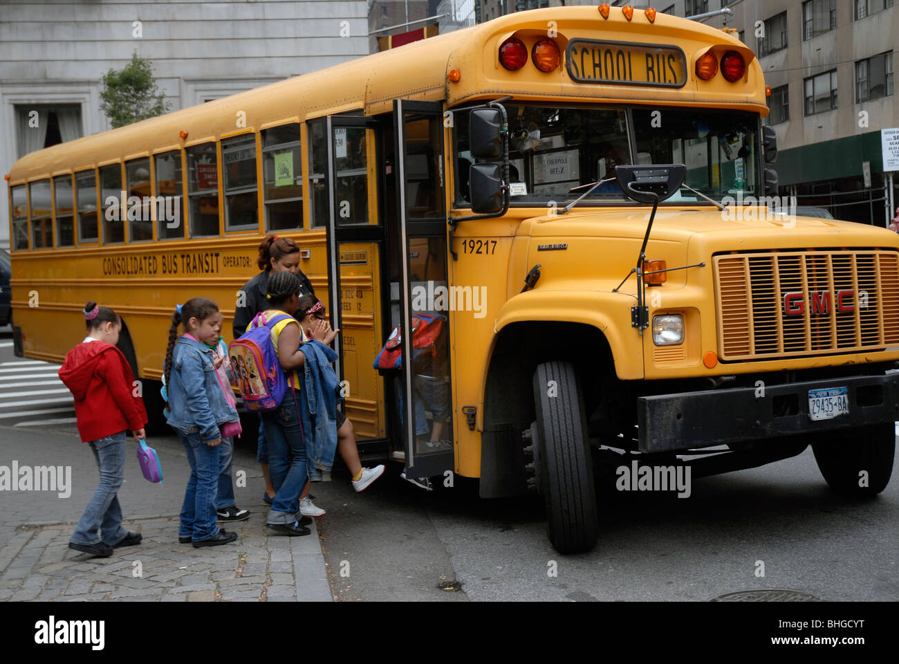 New York City School children getting onto for bus to take them home - Stock Image