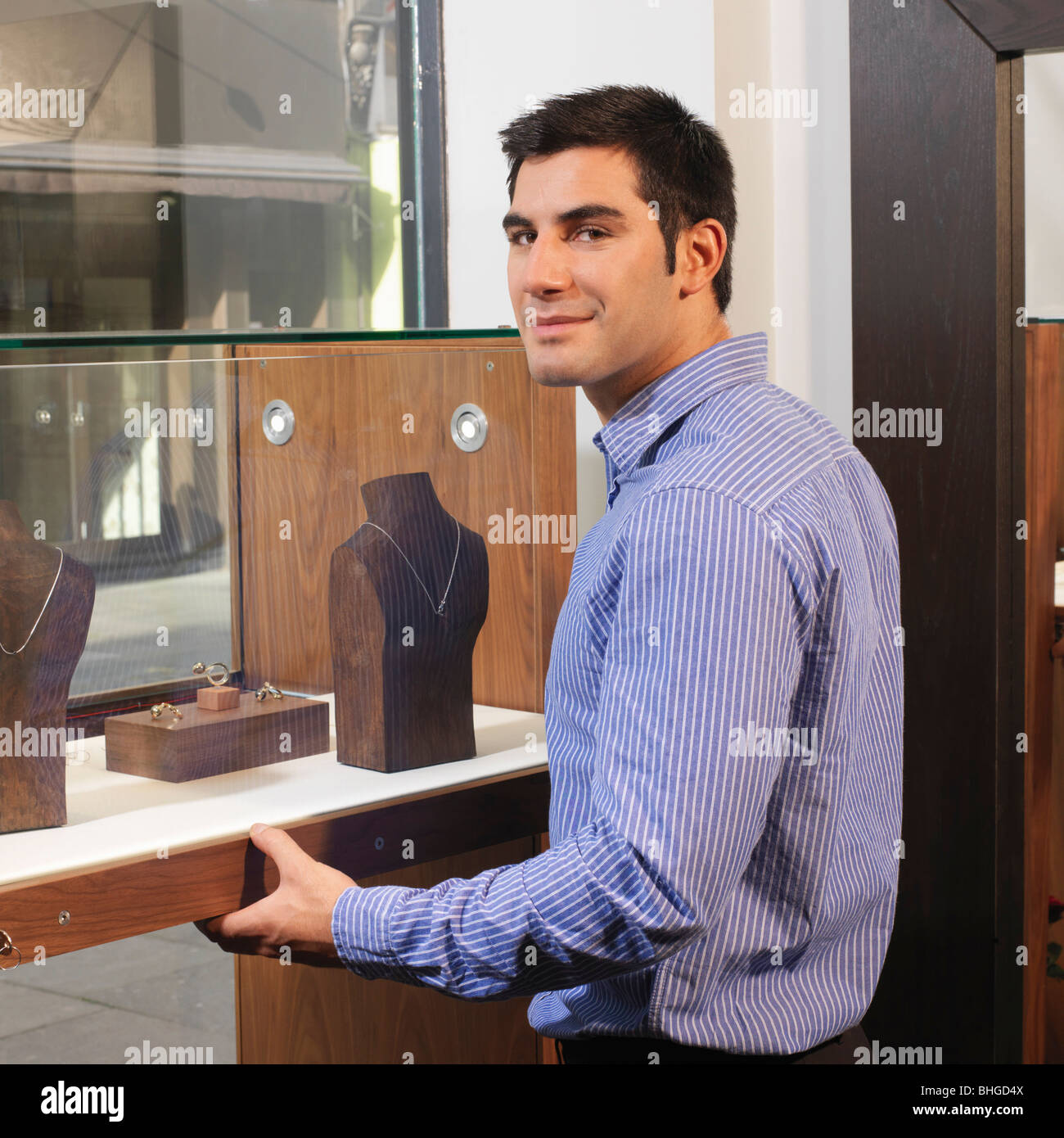 man opening/closing display cabinet - Stock Image