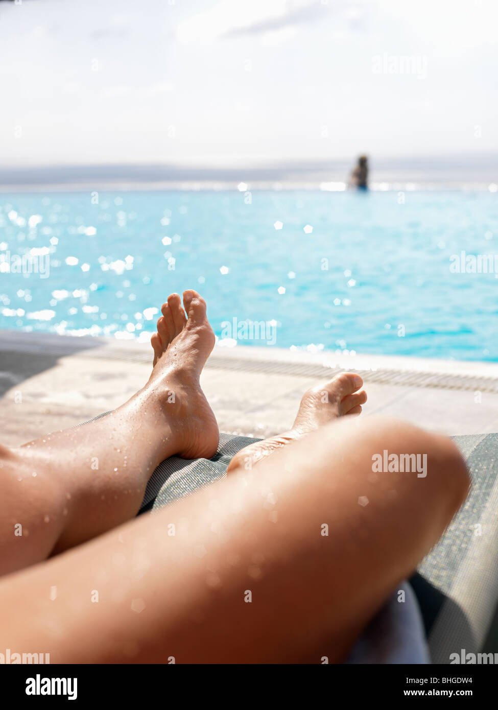 Woman sunbathing by a swimming-pool, Turkey. - Stock Image