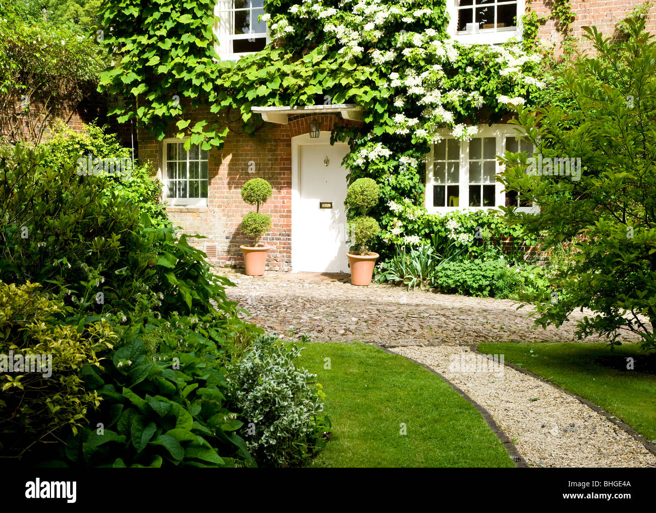 The pretty front door and windows of a typical English country cottage or house, UK - Stock Image