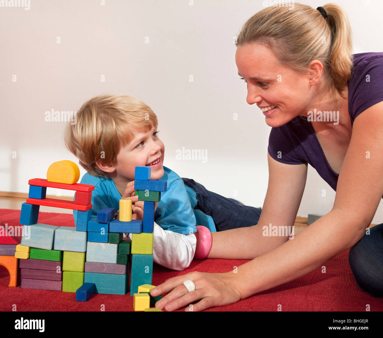 mother and son play with building blocks - Stock Image