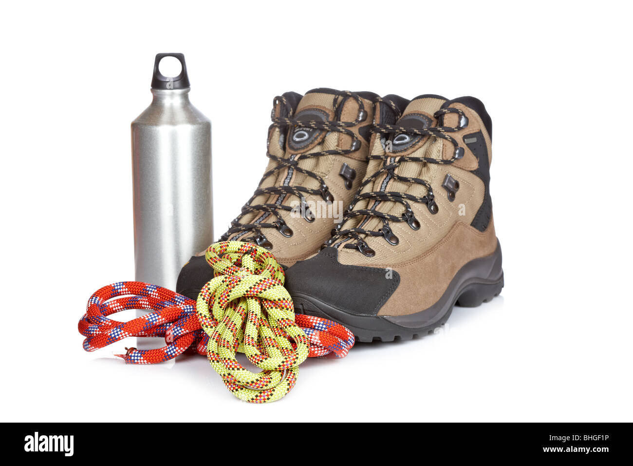 Hiking boots, canteen and ropes reflected on white background. Shallow depth of field - Stock Image