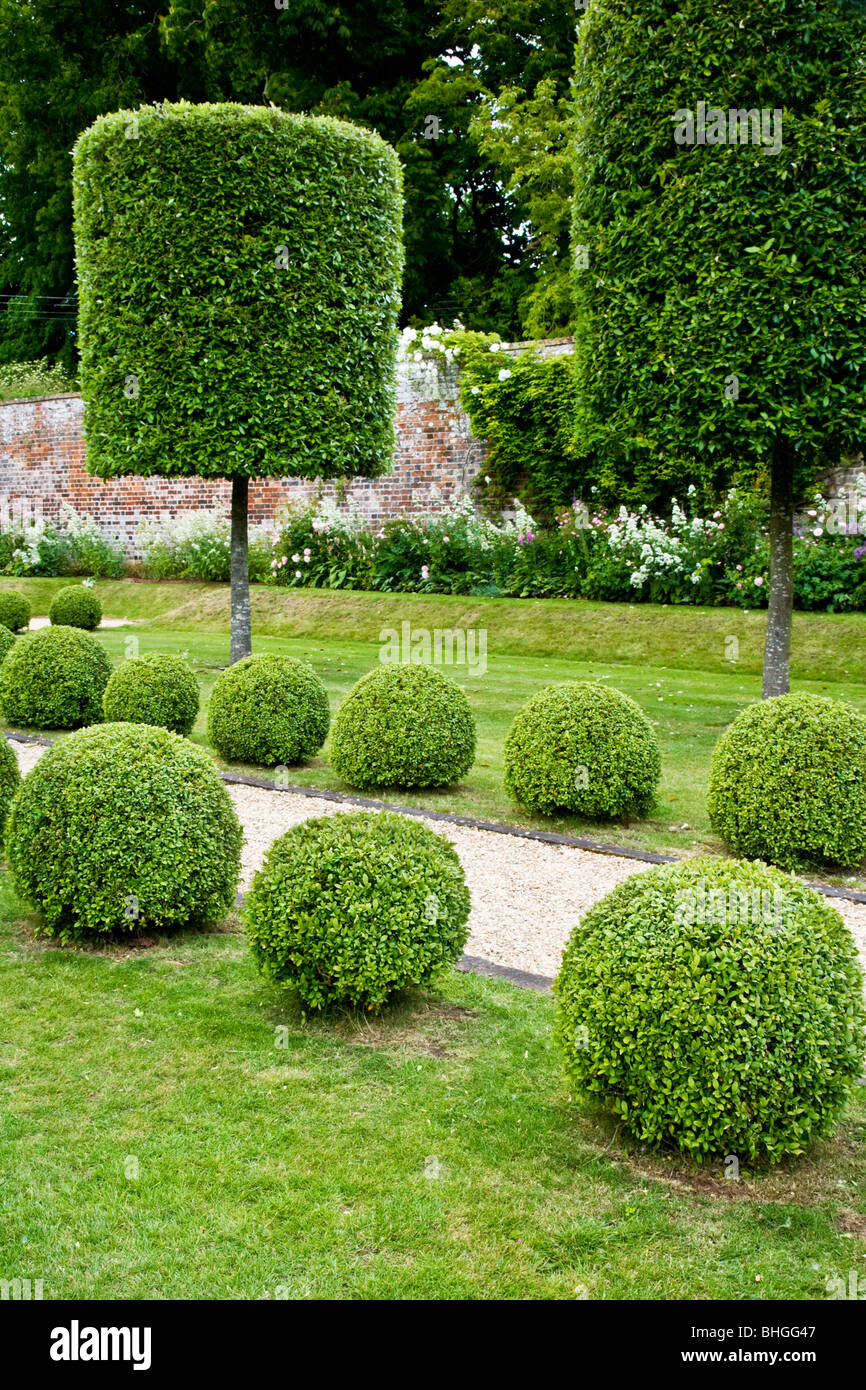 Topiary Trees And Bushes Along A Gravel Path In An English Country