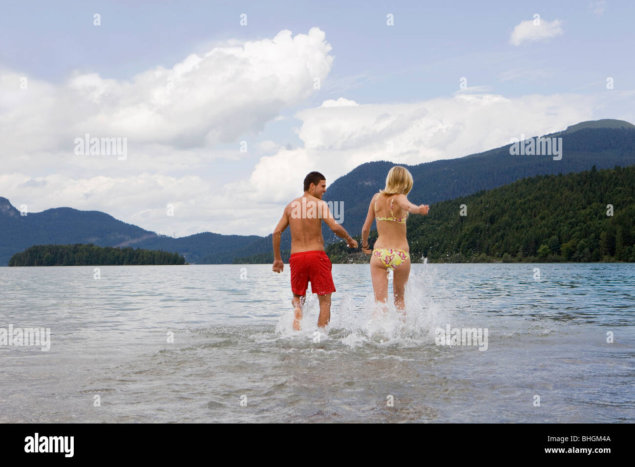 A couple running into the water - Stock Image