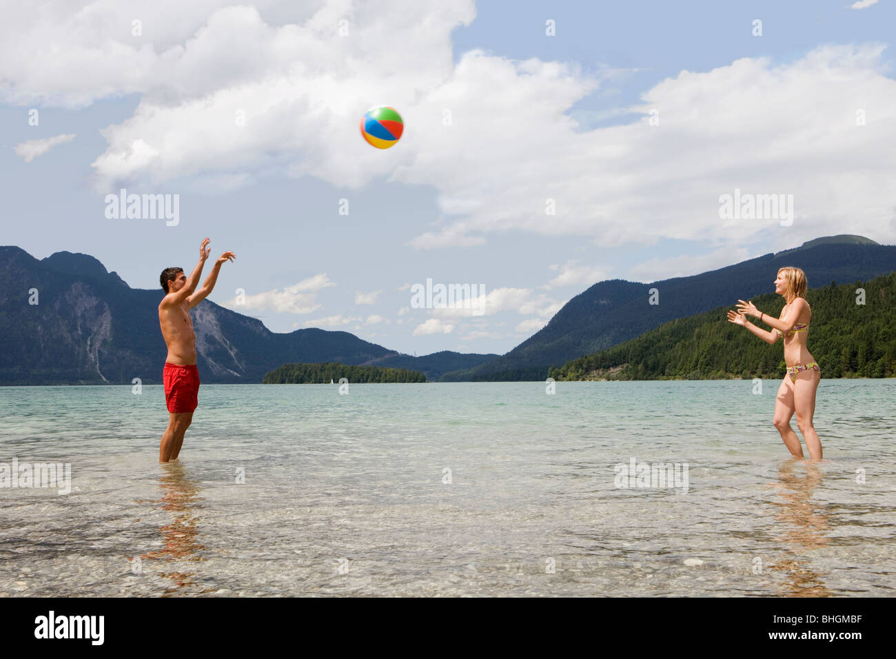 A young couple playing with a beach ball - Stock Image