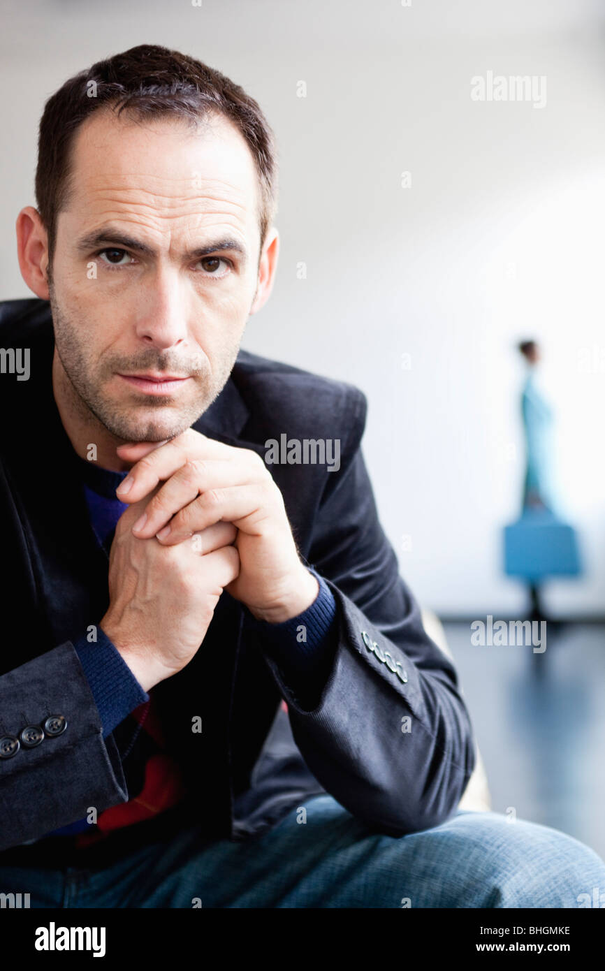 man in front with woman in background - Stock Image