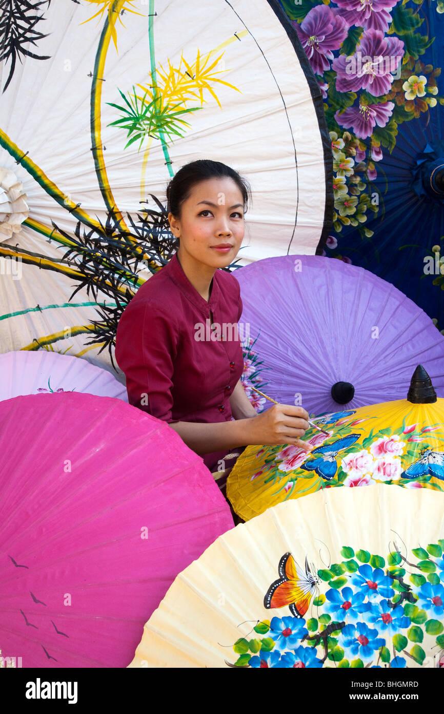 Female painter painting parasol designs,Bor Bo Sang Factory Umbrella Village, Sankampaeng Road, Chiang Mai, Northern - Stock Image