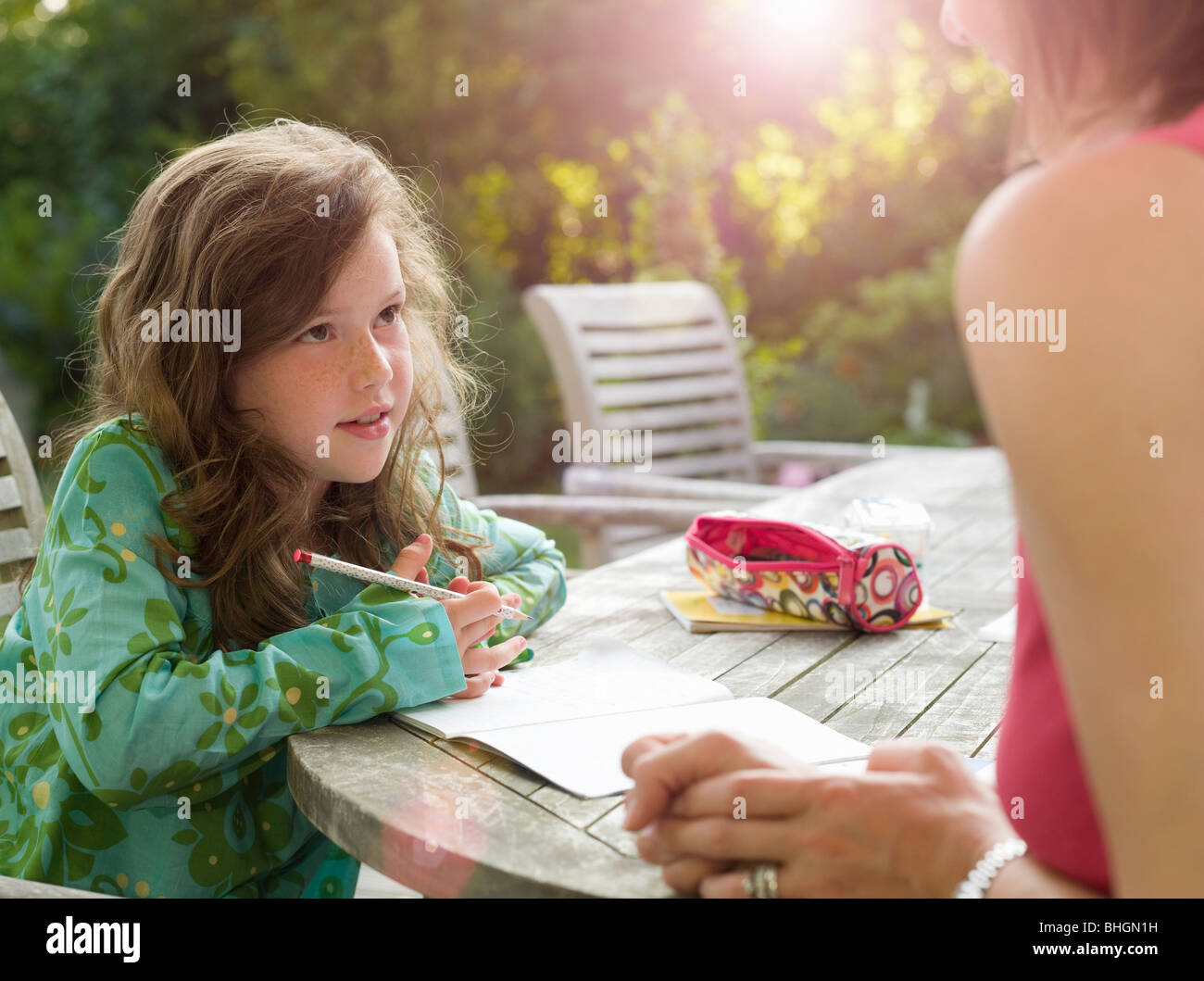 Young girl and mother chatting in garden - Stock Image