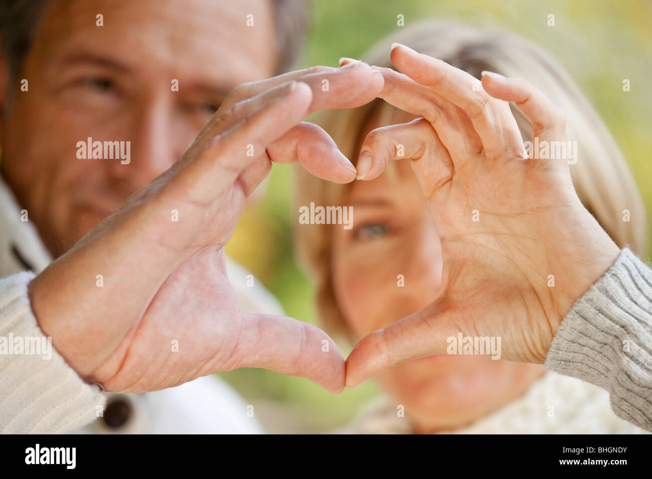 Couple forming heart with their fingers - Stock Image