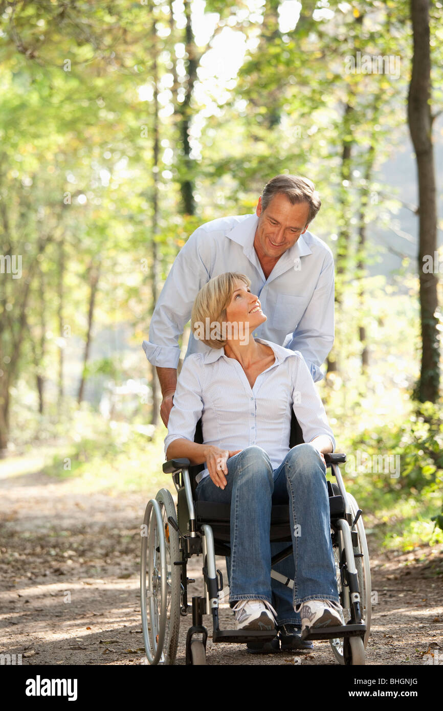 Man pushes woman in a wheelchair - Stock Image