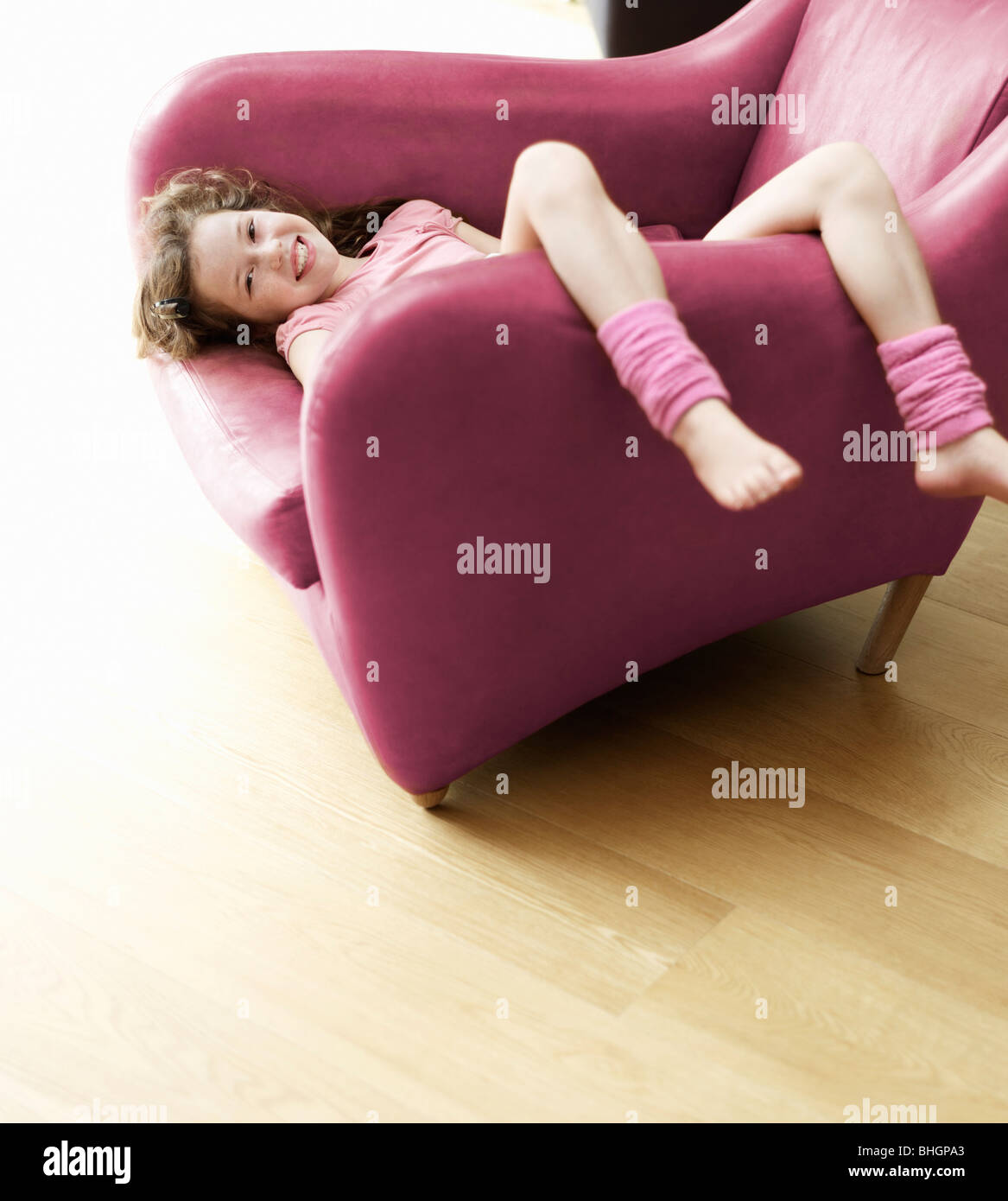 young girl relaxing upside-down in chair - Stock Image