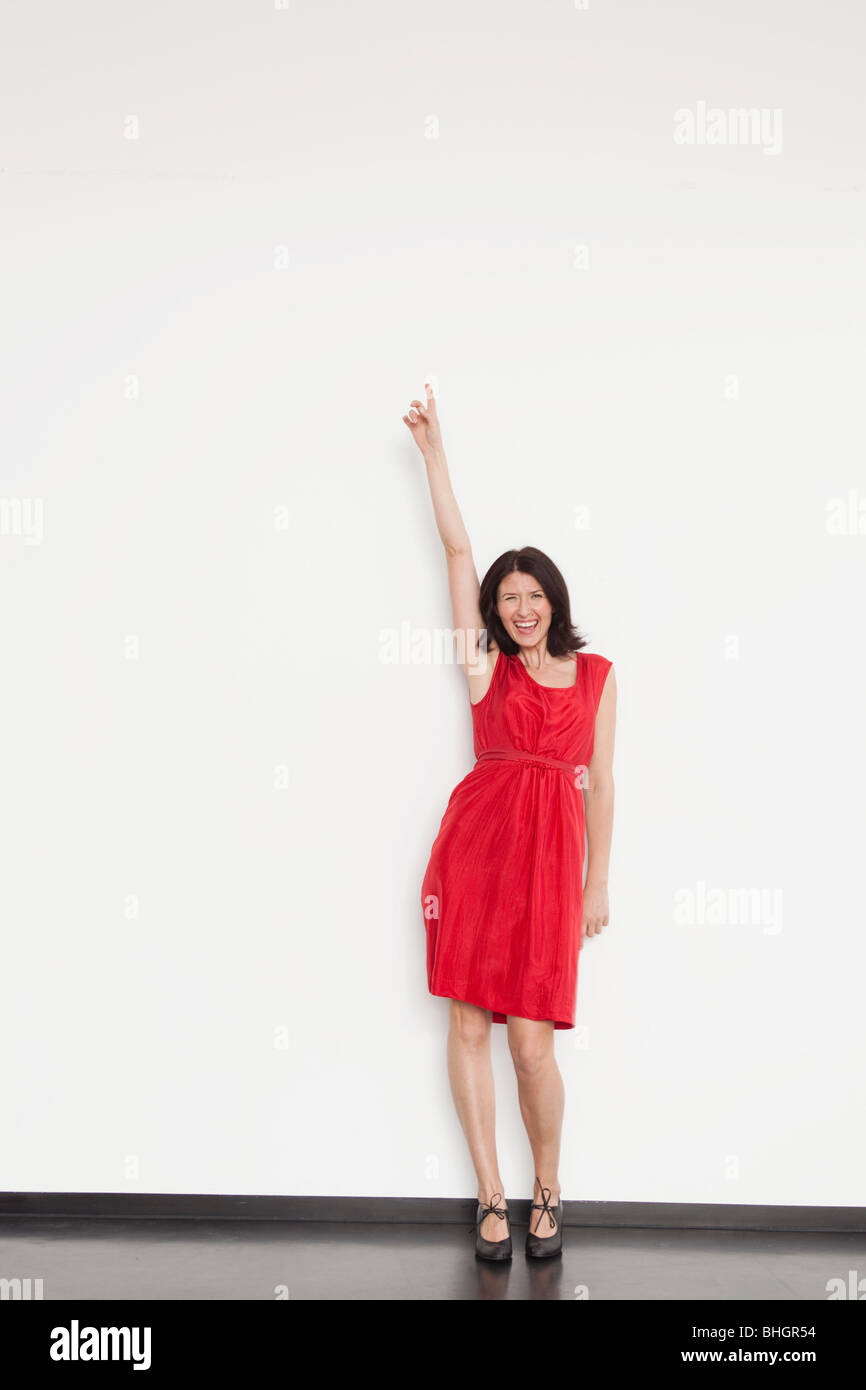 woman pointing upwards with her finger - Stock Image