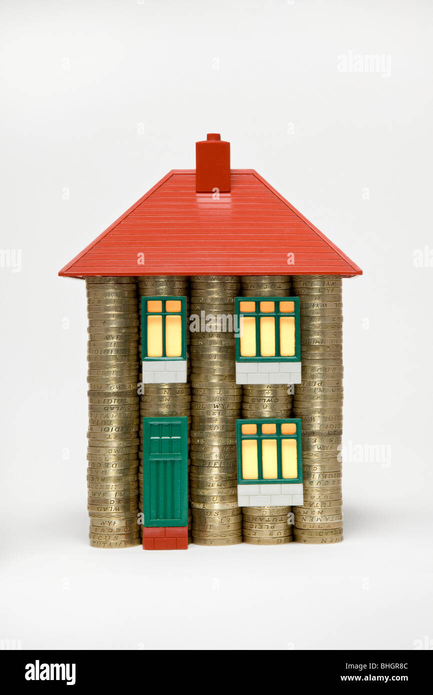 A house made of stacks of pound coins and parts of a 60's Bayko toy house with glowing light effect in windows - Stock Image