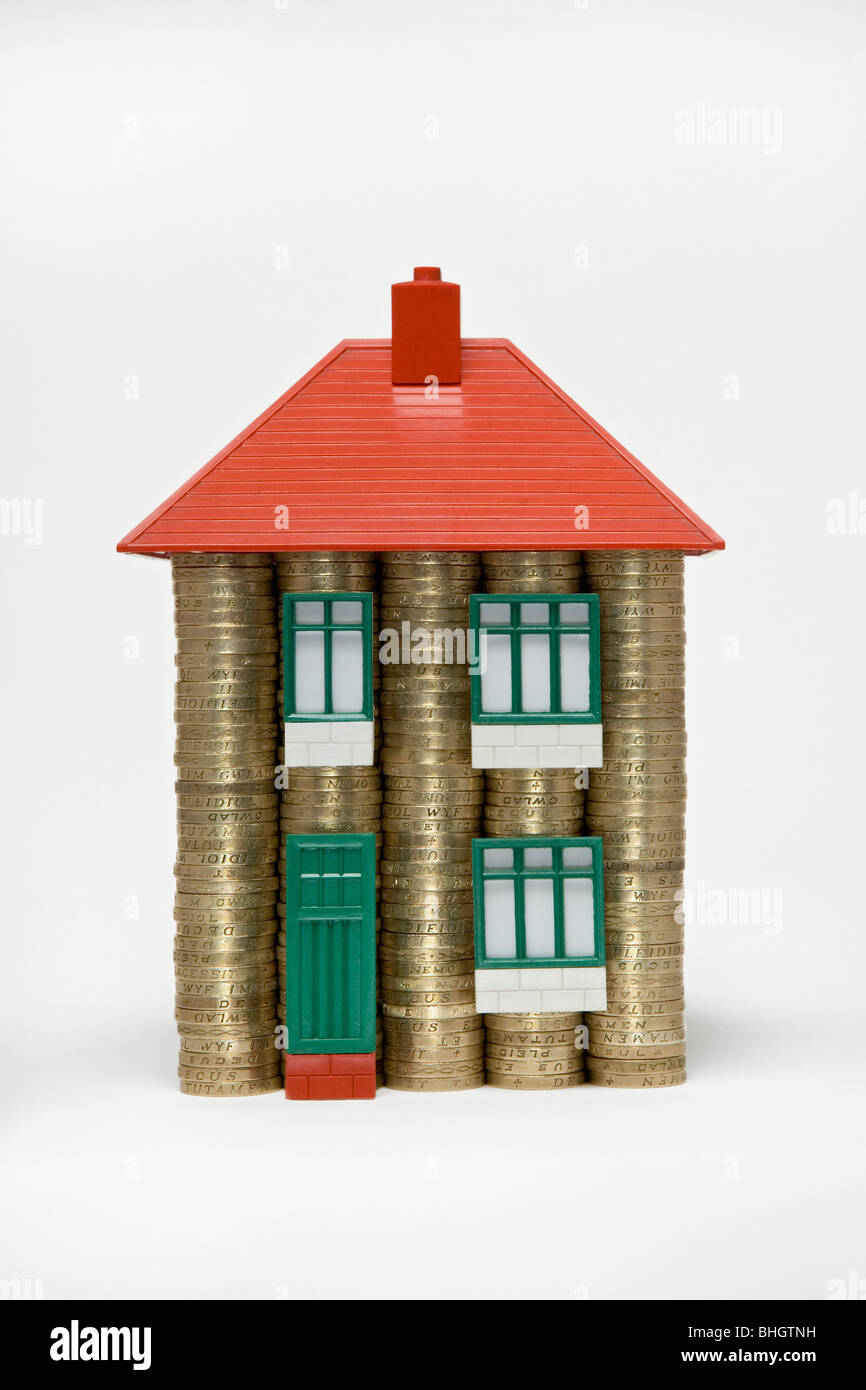 A house made of stacks of pound coins and parts of a 60's Bayko toy house - Stock Image