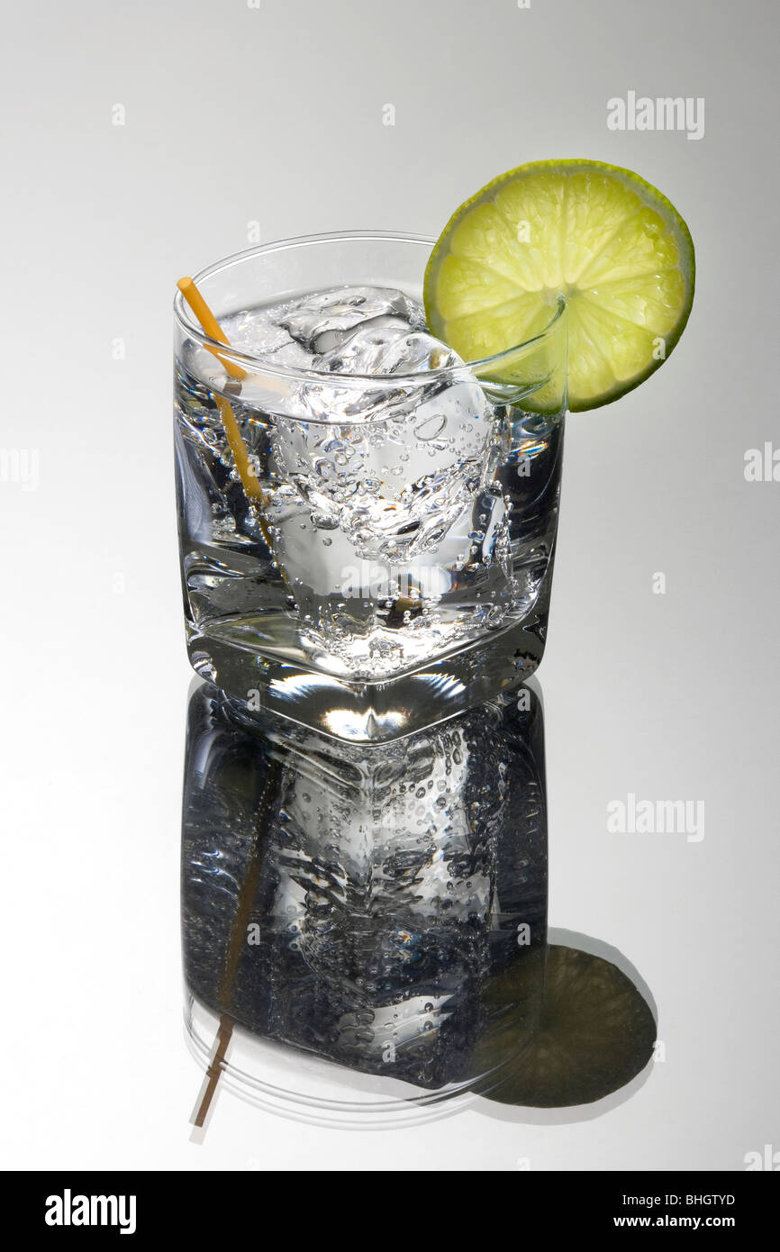 Gin or Vodka and club soda or tonic mixed drink with lime slice garnish on a grey background - Stock Image