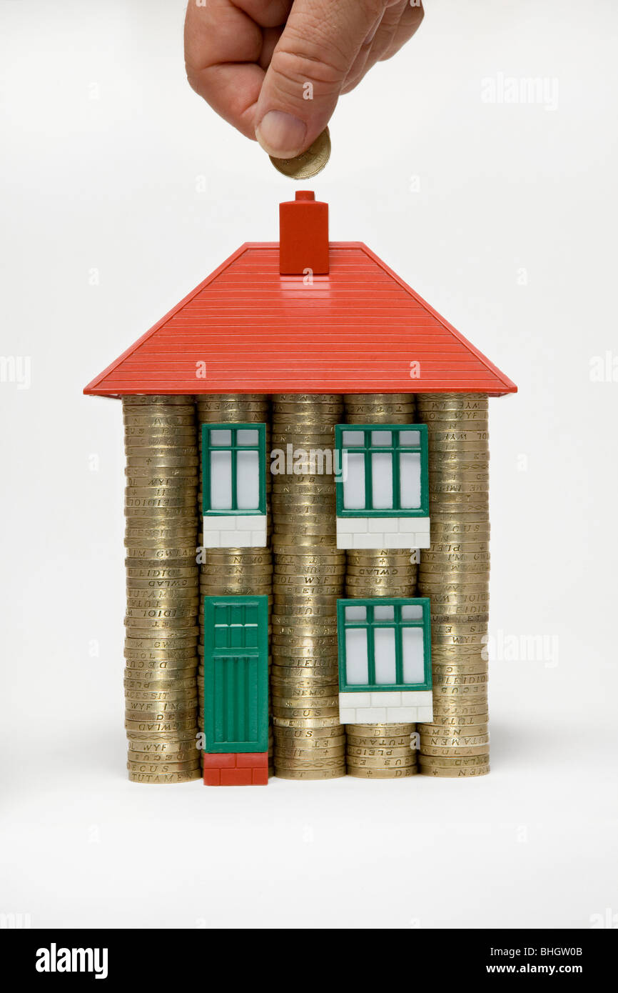 A house made of stacks of pound coins and parts of a 60's Bayko toy house with hand putting money in - Stock Image