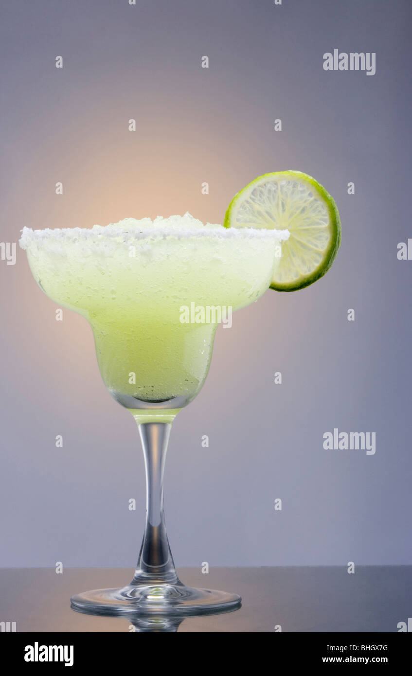 Frozen Margarita mixed drink with lime slice garnish on plain gray background with reflection Stock Photo