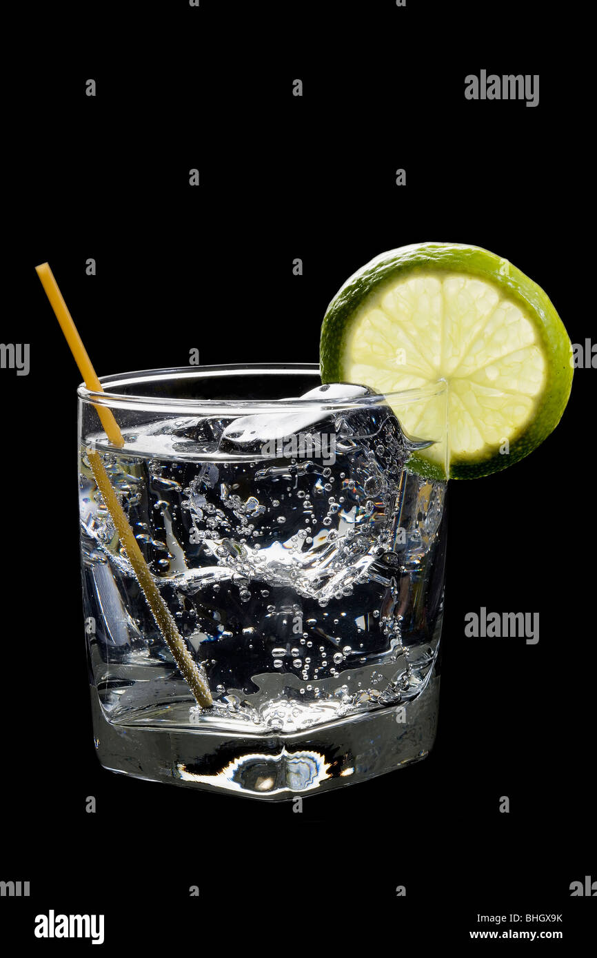 Club soda or Gin or Vodka and tonic with lime slice garnish on a black background - Stock Image