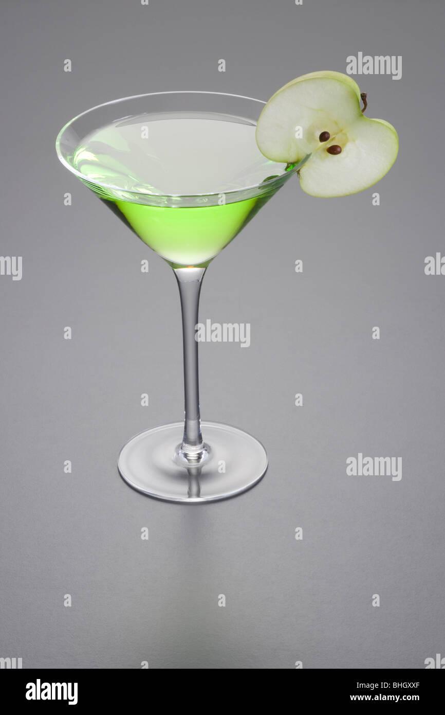 Apple Martini mixed drink with apple slice garnish on grey background - Stock Image