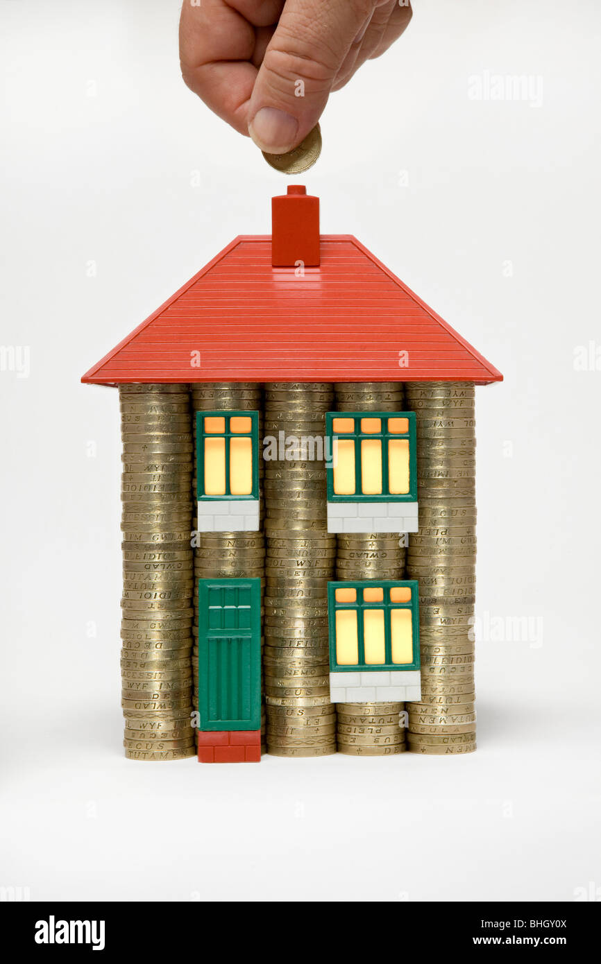 A house made of stacks of pound coins and parts of a 60's Bayko toy house with glowing light in windows and - Stock Image