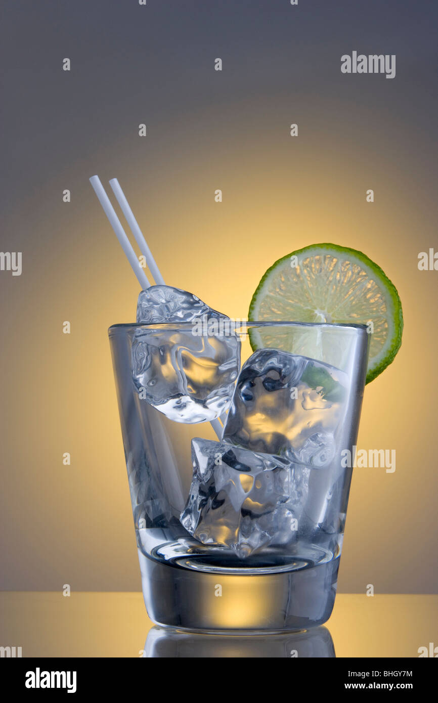 Empty tumbler with ice cubes, straws and lime slice garnish on plain background - Stock Image