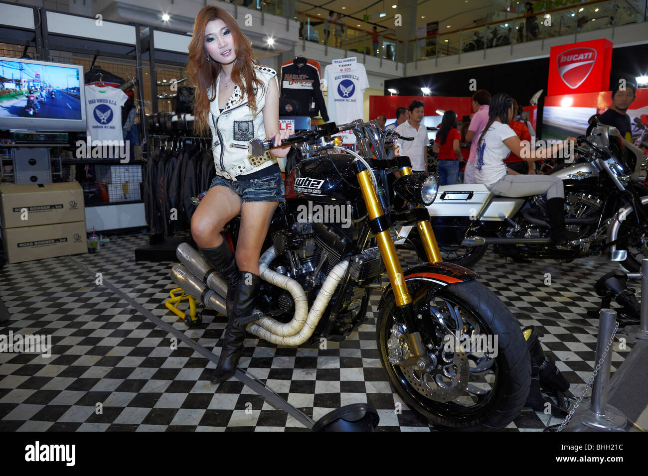 Harley Davidson customized chopper and female model at the annual Bangkok motorcycle show. Thailand S. E. Asia - Stock Image