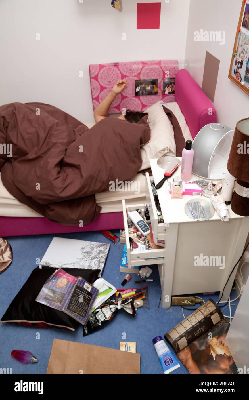 A teenage girl asleep in her messy bedroom - Stock Image