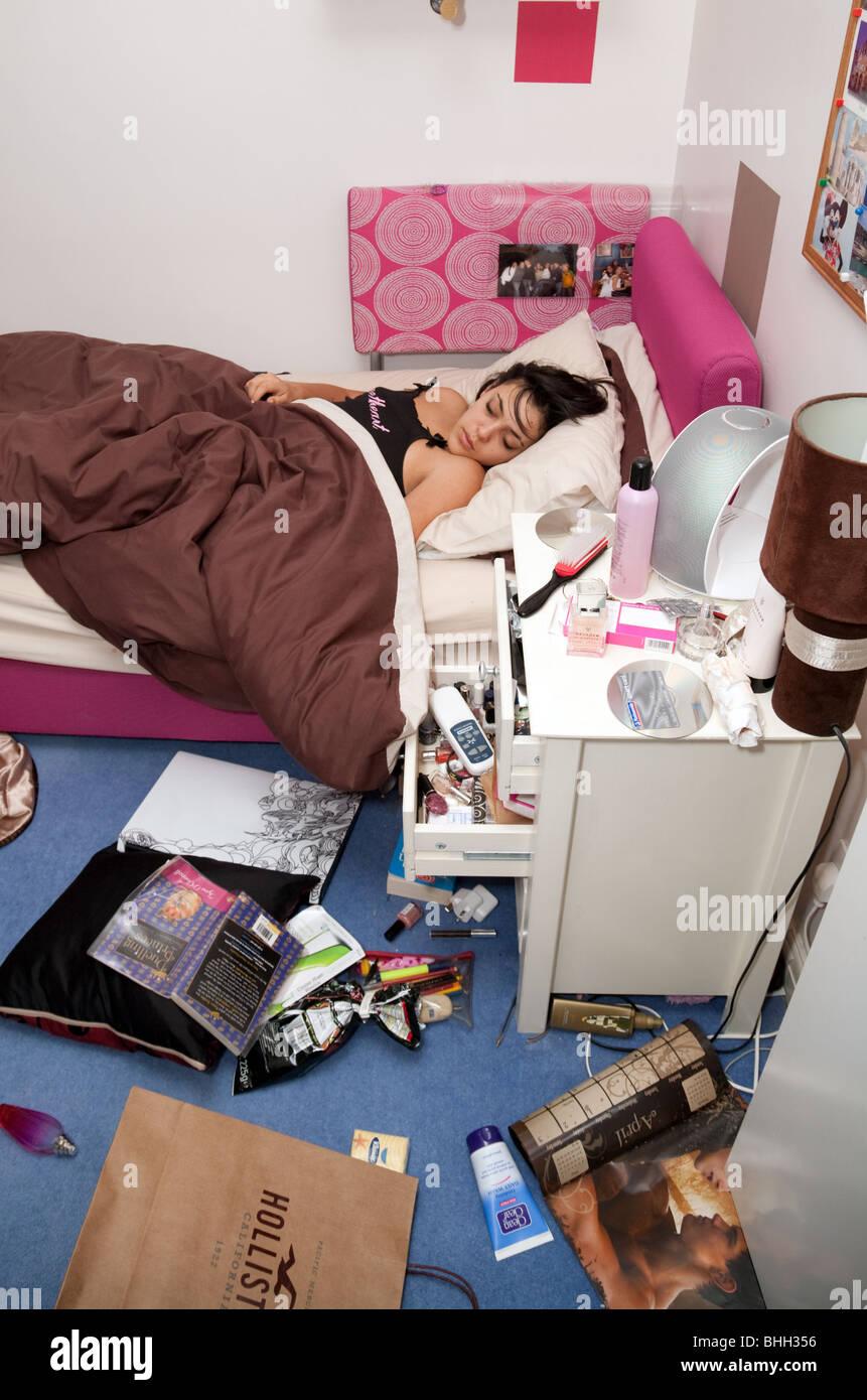 A teenage girl asleep in her messy bedroom, Suffolk UK - Stock Image