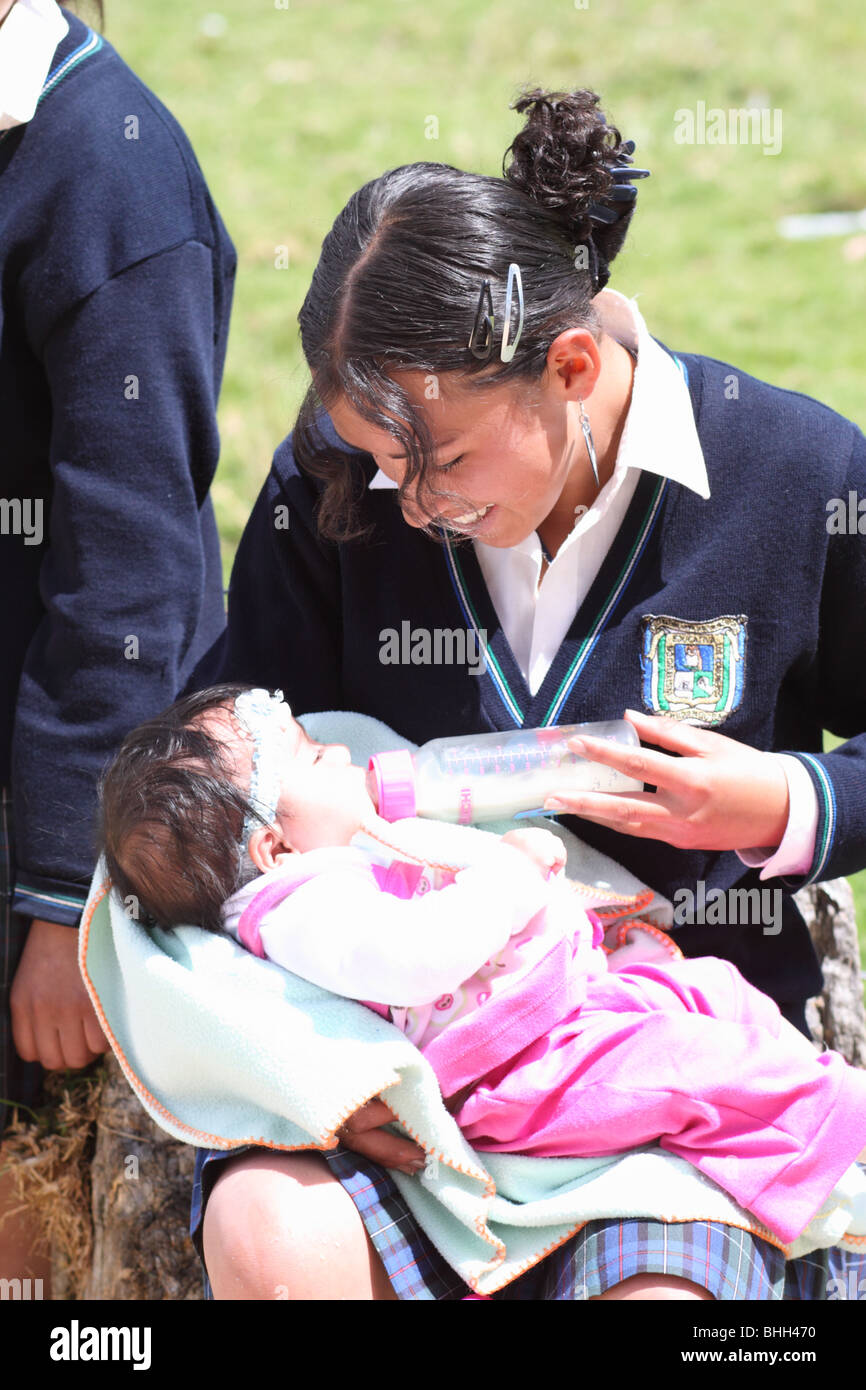 Teenager feeding her son in the courtyard in the school.  Chiquinquirá, Colombia, South America - Stock Image