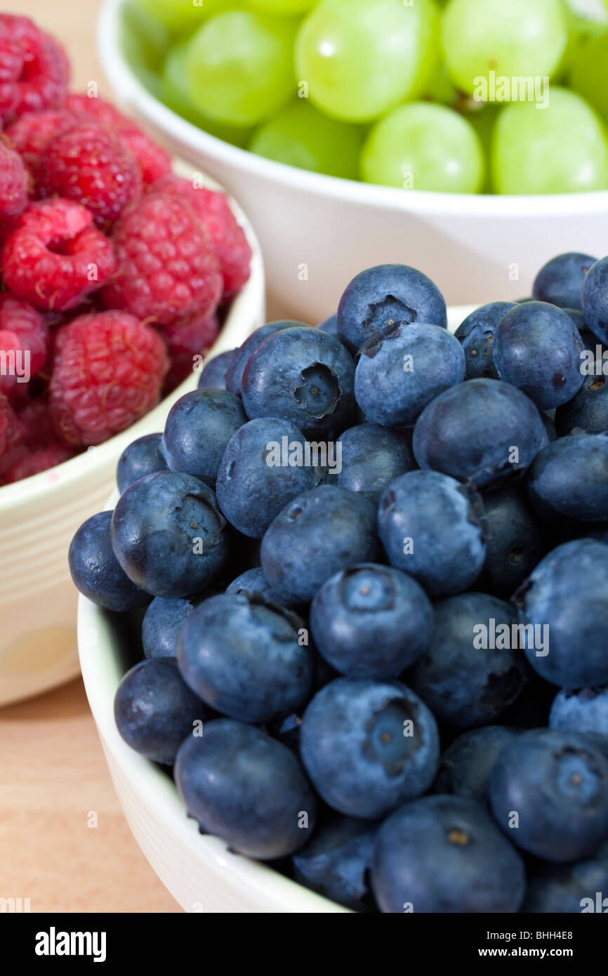 Three bowls of healthy breakfast berries, raspberries, blueberries and grapes - Stock Image