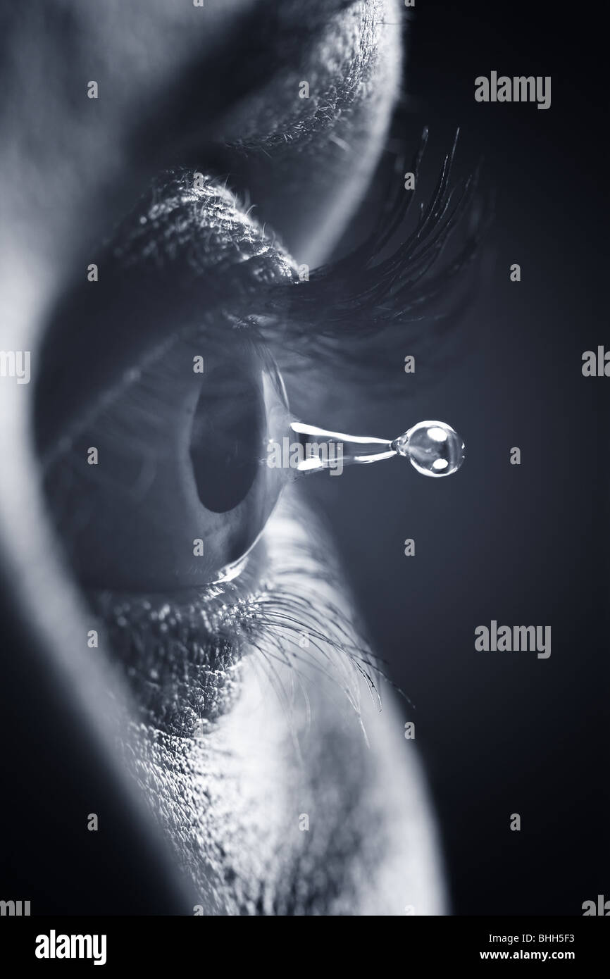 Macro on eye with tears water droplet - Stock Image
