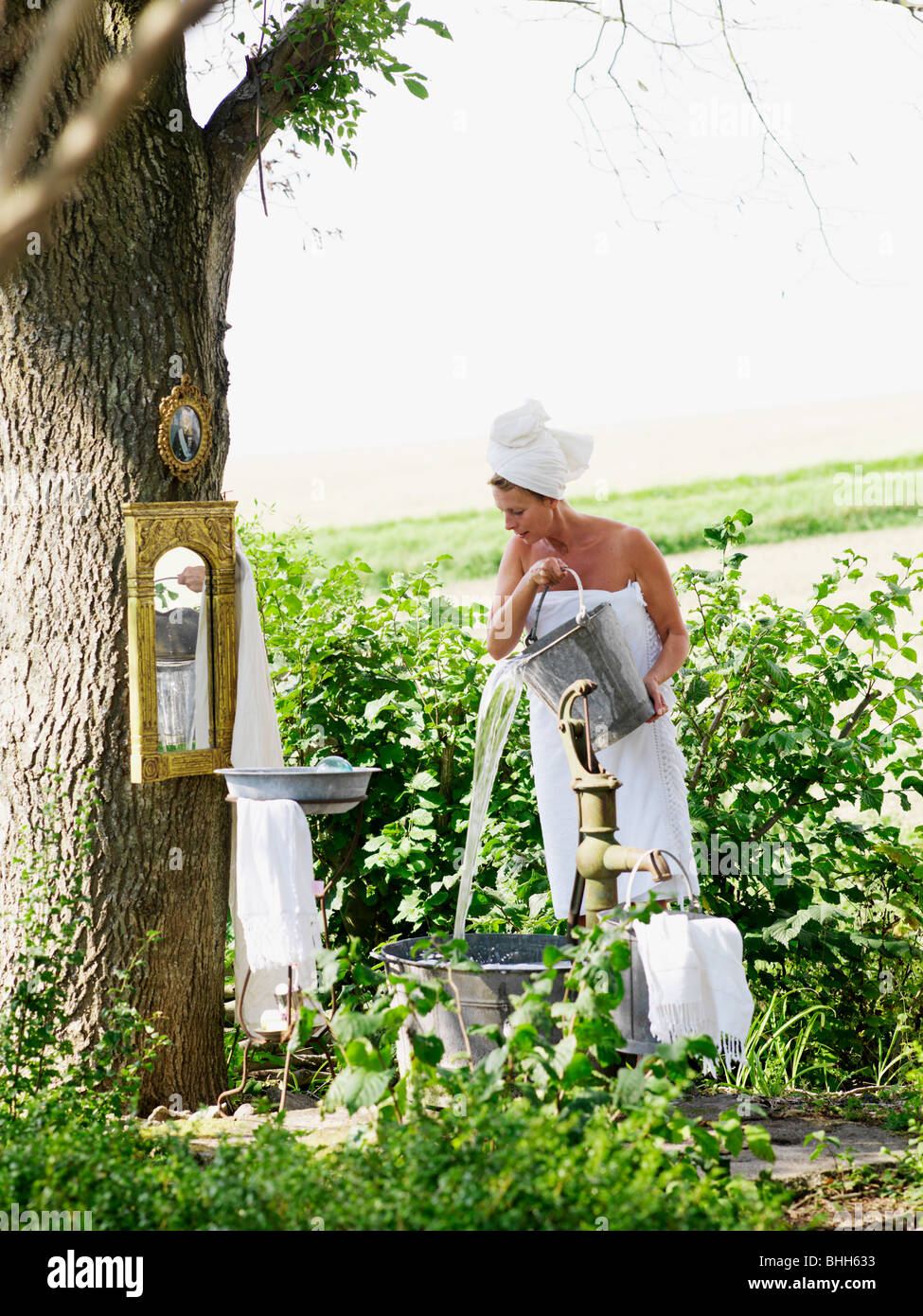 Woman taking a bath in a garden, Sweden. Stock Photo