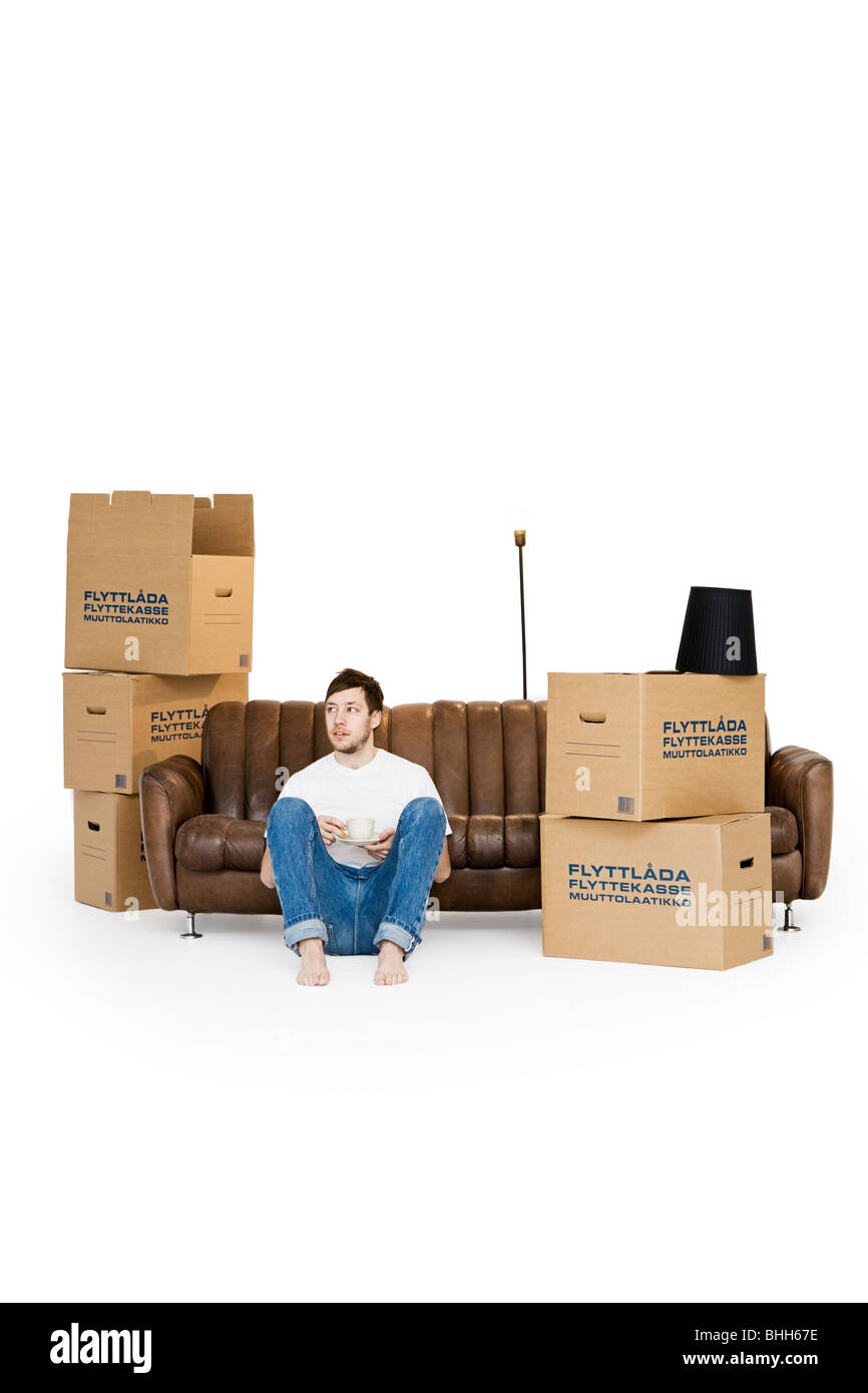 Young man by a couch and boxes. - Stock Image