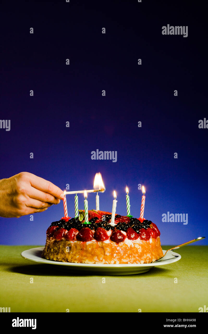Candles on a birthday cake. - Stock Image
