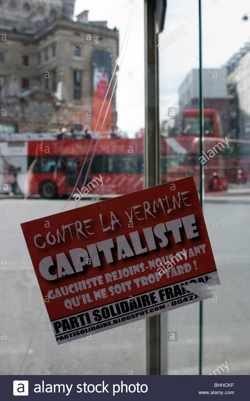 An anti capitalist political protest sticker on a phone booth in Boulevard Haussmann Paris - Stock Image