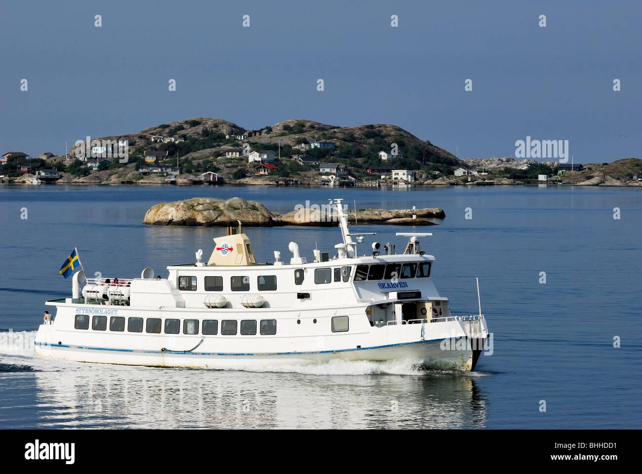 A passenger steamer passing an island, Sweden. - Stock Image