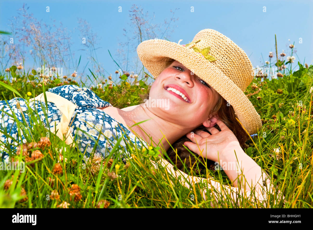 Young teenage girl laying on summer meadow amid wildflowers in straw hat - Stock Image