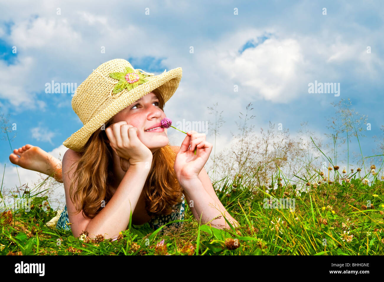 Young teenage girl laying in summer meadow resting chin on hand smelling flower Stock Photo
