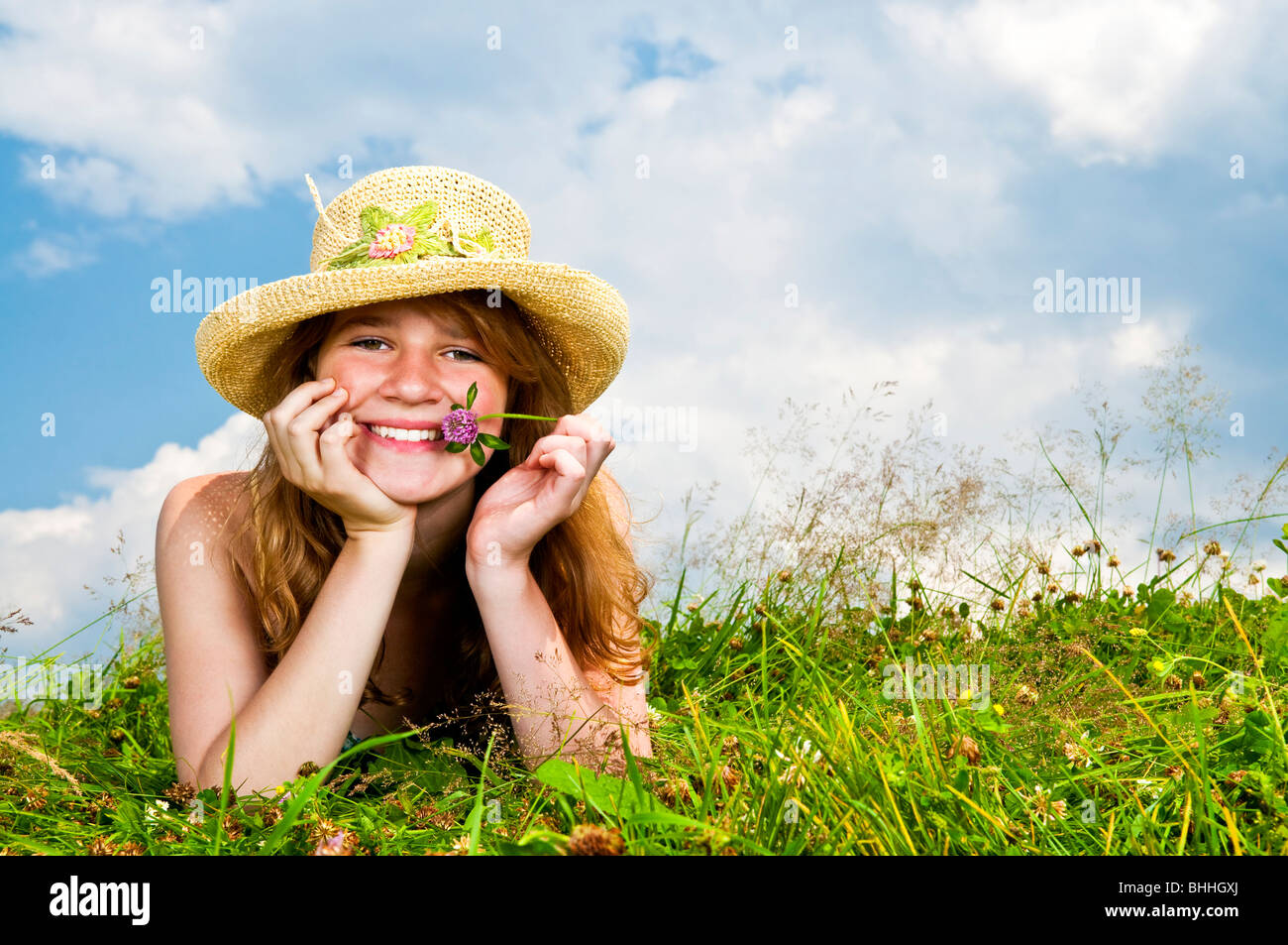 Young teenage girl laying in summer meadow resting chin on hand holding flower Stock Photo